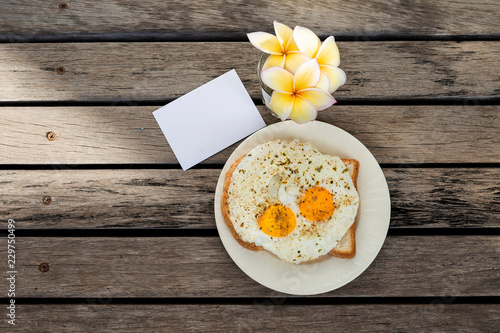 Fried Eggs On Toast With White Paper Card And Flower On Wooden