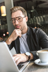 handsome young freelancer working with laptop in cafe and looking at camera