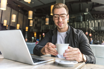 close-up shot of handsome young freelancer with laptop holding cup of coffee in cafe