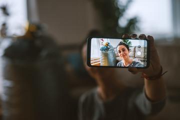 Woman taking selfie in living room. Selective focus on smart phone.