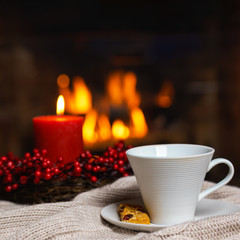 Cup of hot drink with cookie berries and red candle in red Christmas decoration on cozy knitted plaid in front of fireplace. Christmas New Year concept. Cozy relaxed magical atmosphere home interior.