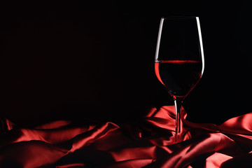 Glass of red wine with shiny cloth on dark background