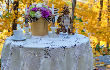 Decorated table in a street cafe against the background of autumn.