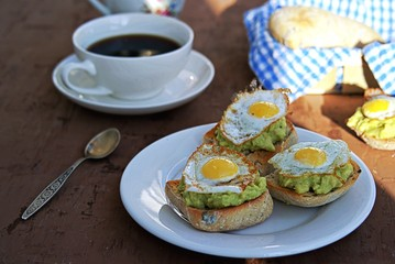 Healthy breakfast, toast with avocado mash and fried quail egg on a brown background.