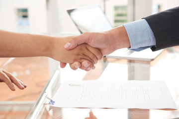 Close-up of two business partners shaking hands with each other near the contract lying on the table
