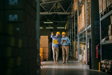Two successful smiling business man walking through big warehouse with helmets on their heads.Younger man is shoving older one shelf's full of products ready to be delivered. Happy investors.