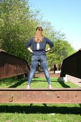 entschlossene junge Frau stehend auf einer Schiene in rückansicht