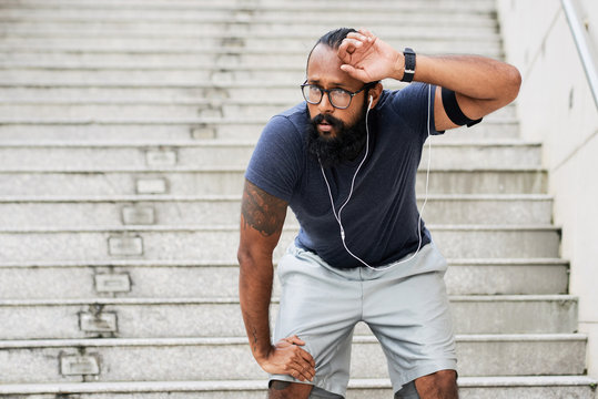 Bearded tattooed Indian male athlete standing on steps outdoors, wiping sweat from his forehead and recovering breath after running