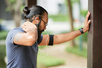 Side view of athletic dark-haired bearded man doing warming up exercises outdoors and listening to music through earphones
