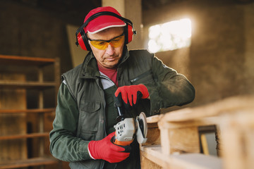 Picture of mature carpenter man in protective uniform shaping wood with electric grinder. Enjoying his job in his working garage on sunny day.