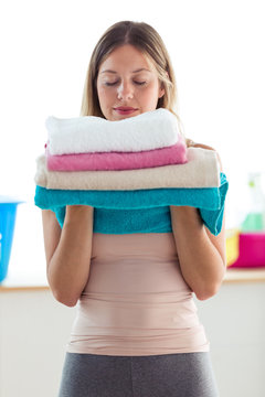 Beautiful young woman holding and smelling clean towels at home.