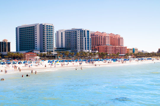 Tropical sandy beach vacation city Clearwater Beach in Florida, colourful beachfront hotel resorts buildings, palm trees, sunbathing tourists, turquoise blue sea waters of Mexican Gulf