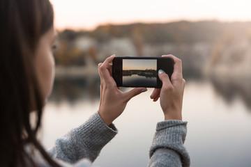 Młoda dziewczyna robi zdjęcia telefonem komórkowym. Hobby. Krajobraz.  Technologia