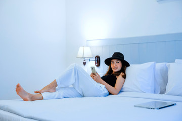 portrait of young attractive woman lying in bed smiling in holiday for start travel day