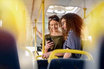 Two girlfriends standing in a bus and talking. Traveling together to the school. Looking at the telephone and having fun.