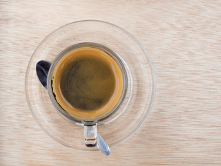 Hot coffee in clear glass on wooden floor in the morning. Top view