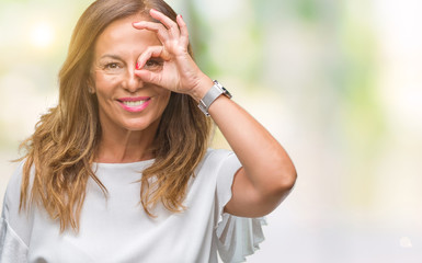 Middle age senior hispanic woman over isolated background doing ok gesture with hand smiling, eye looking through fingers with happy face.