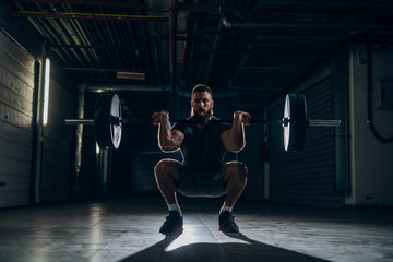 Muscular attractive caucasian bearded man doing front barbell squat in underground hallway.  Storage units and pipes in background.