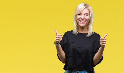 Young beautiful blonde woman over isolated background success sign doing positive gesture with hand, thumbs up smiling and happy. Looking at the camera with cheerful expression, winner gesture.