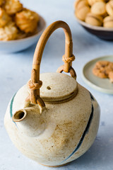 Detail of teapot, different types of biscuits on a delicate blue background