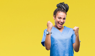 Young braided hair african american girl professional nurse over isolated background very happy and excited doing winner gesture with arms raised, smiling and screaming for success Wall mural