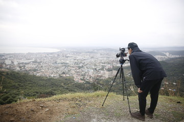 Photographer take a photo of city landscape on a hill