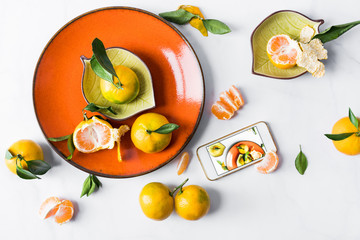 Still life with tangerines on an orange plate on a white background with a smartphone. Concept foodbloger.