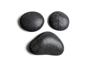 Three big black pebbles forming a triangle, isolated on white background