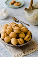 Baci di dama': delicious chocolate cookies with hazelnuts and topping on delicate background