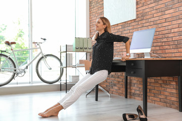 Young businesswoman stretching at workplace. Productivity boost