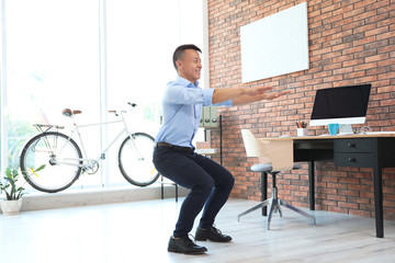 Young businessman doing exercises in office. Workplace fitness
