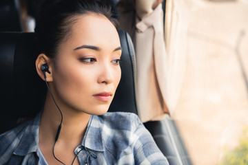 close up portrait of asian woman listening music in earphones and looking away during trip on travel bus