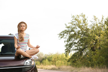 Young woman meditating on car hood outdoors. Joy in moment