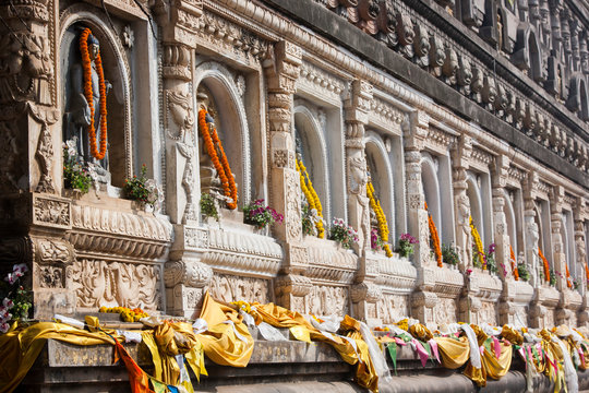 Buddha sculpture with french marigolds offered by pilgrims on the Mahabodhi Temple, Bodhgaya, Gaya, Bihar State, India