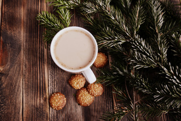 Coffee with milk, hot chocolate or cocoa with cinnamon stick in a Cup and fir branches. Winter hot drink for cold weather. New year and Christmas concept