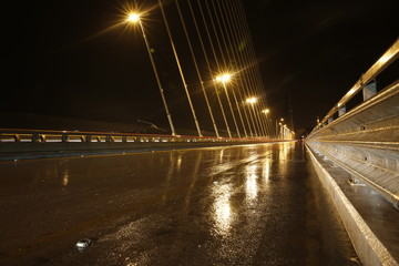 Big Cable-stayed bridge at night with rain reflection