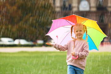 Wall Mural - Cute little girl with bright umbrella in park