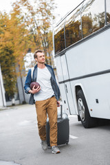 handsome man with backpack and rugby ball carrying bag on wheels near travel bus at street