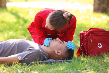 Woman in uniform checking for breathing of unconscious man outdoors. First aid