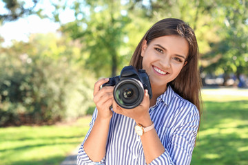 Young female photographer with professional camera in park