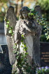 Closeup of stoned angel with ivy leaves on tomb in cemetery