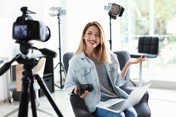 Female photo blogger recording video on camera indoors