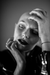 Emotive portrait of a beautiful bald woman while covering her face with her hands.