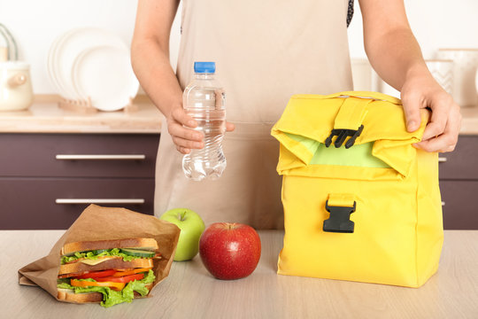 Woman packing food for her child at table in kitchen, closeup. Healthy school lunch