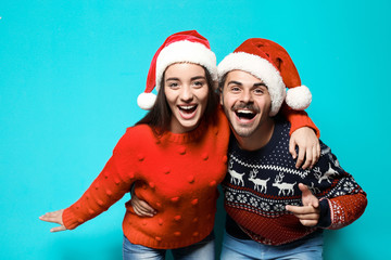 Young couple in warm sweaters and Christmas hats on color background