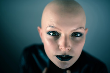 Emotive portrait of a beautiful bald woman while standing in the studio and wearing a black leather jacket.