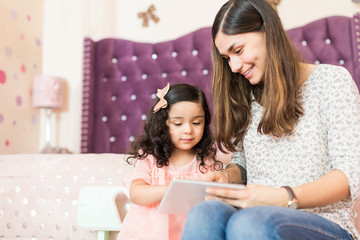 Nanny Assisting Girl In Using Tablet PC