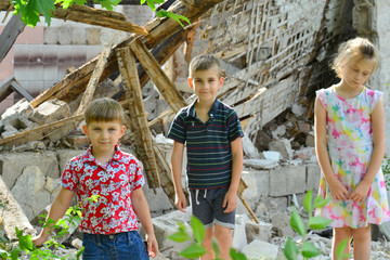 Children are near the ruined house, the concept of natural disaster, fire, and devastation.