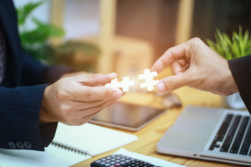 People putting two pieces of jigsaw together,Hands of business people hold paper jigsaw puzzle and solving puzzle together,Business team assembling Jigsaw puzzle,jigsaw concept,for website banner