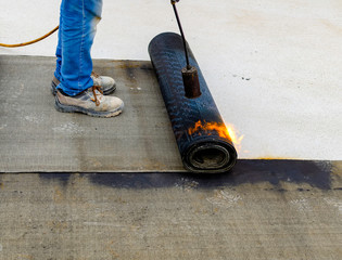 Worker preparing part of bitumen roofing felt roll for melting by gas heater torch flame.